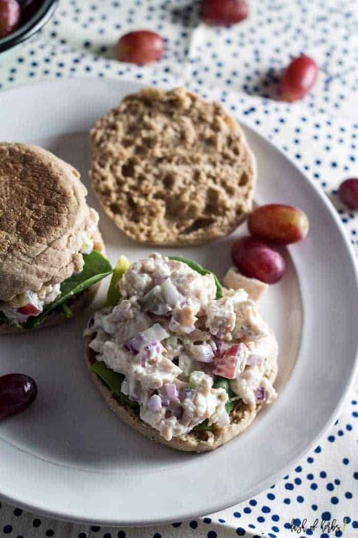 This is an overhead image of the Easy Chicken Salad Sandwiches recipe.  The chicken salad is on a toasted English muffin with whole grapes on a white plate.  There is a navy blue polka dot napkin underneath the plate.