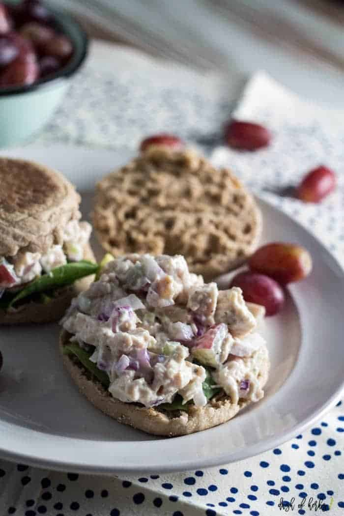 This image of the Easy Chicken Salad salad recipe shows the recipe on a toasted English muffin. This chicken salad recipe has chopped grapes, chopped cooked chicken, finely chopped red onion and Greek yogurt. There is a small light blue bowl filled with grapes in the background.