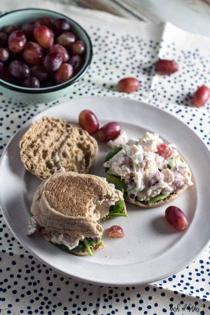 This is an overhead image of the Easy Chicken Salad Sandwiches recipe.  The chicken salad is on a toasted English muffin with whole grapes on a white plate.  There is a bite taken out of the sandwich.  There is a navy blue polka dot napkin underneath the plate.