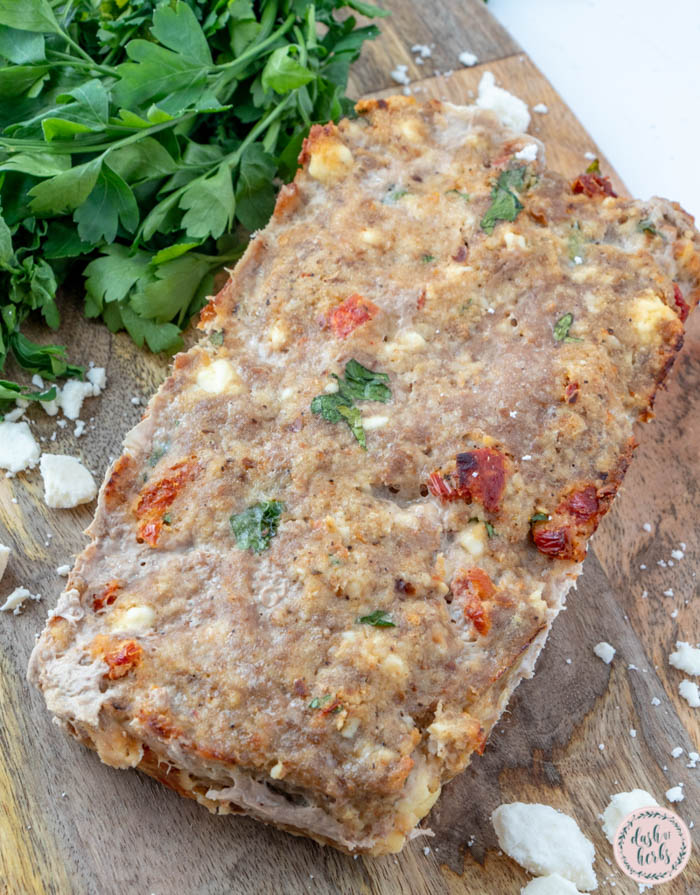 A close up image of the feta and sundried tomato turkey meatloaf recipe in a clear loaf pan. There is fresh parsley in the background.