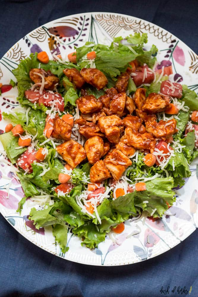 An overhead image of the BBQ Chicken Salad recipe on a colorful plate.  You can see the BBQ chicken, carrots, romaine lettuce, tomatoes and cheese.