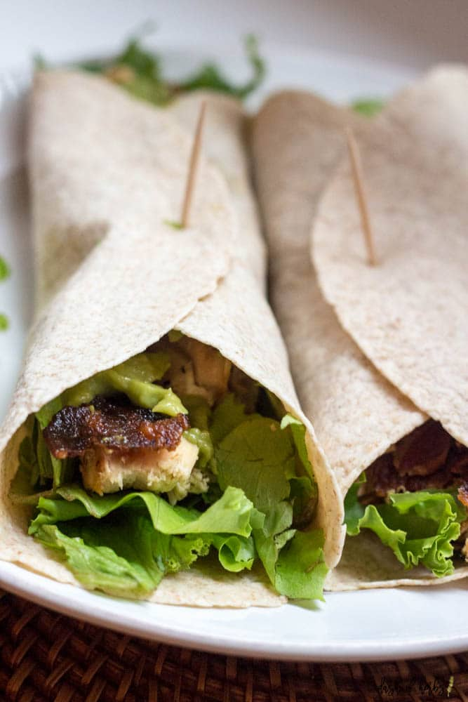 A close up image of the California Chicken Wrap recipe that is on a white plate.  The image has two wraps with grilled chicken, avocado spread, bacon and lettuce.