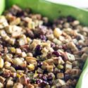 A close up image of the Apple Sausage Cranberry Stuffing recipe in a green colorful ceramic pan. You can see the dried cranberries, apples, stuffing and sausage in the image.