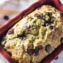 An image of the Chocolate Chip Zucchini Bread recipe with the recipe in a bright red ceramic loaf pan. You can see a yellow and white napkin underneath the loaf pan with chocolate chips sprinkled in the image.