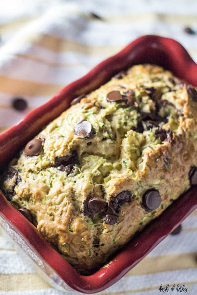 A close up image of the Chocolate Chip Zucchini Bread recipe with the recipe in a bright red ceramic loaf pan.  You can see a yellow and white napkin underneath the loaf pan with chocolate chips sprinkled in the image.