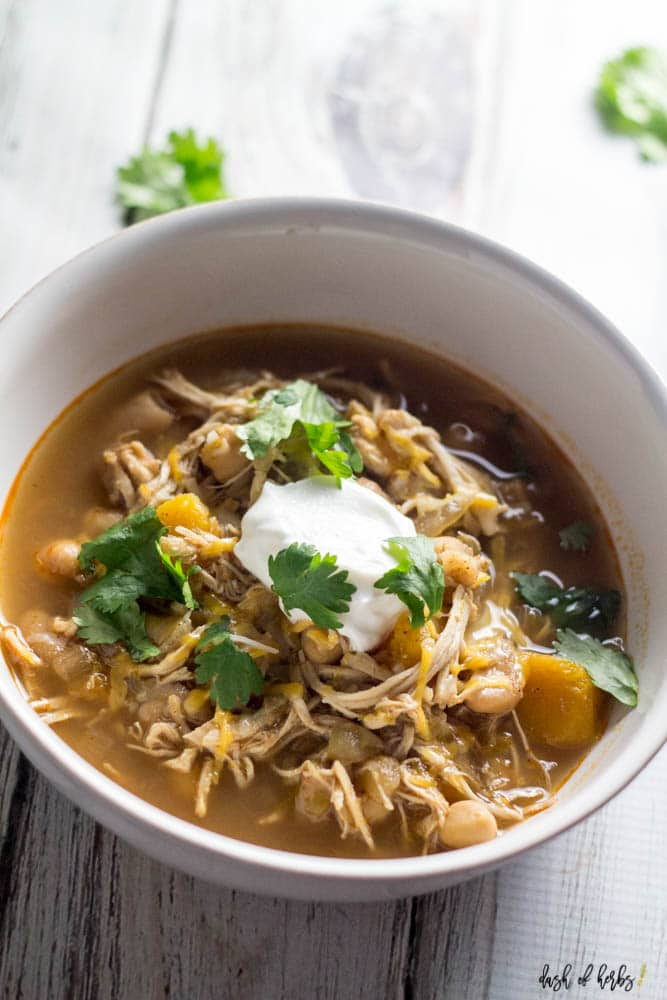 A close up image of the Slow Cooker White Chicken Chili recipe in a white bowl.  The shredded chicken, butternut squash and chickpeas.  The chili is topped with a dollop of Greek Yogurt.