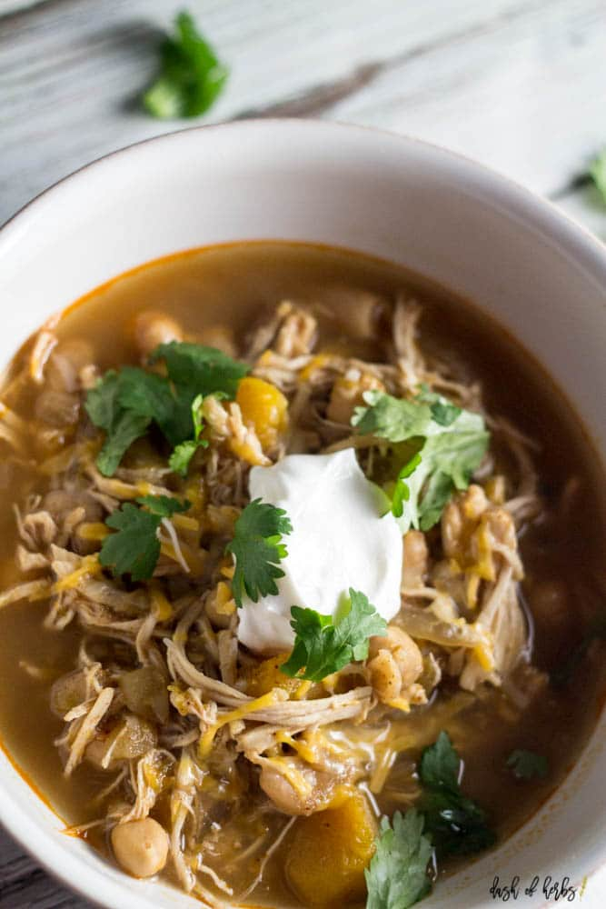 A close up overhead image of the Slow Cooker White Chicken Chili recipe in a white bowl.  The shredded chicken, butternut squash and chickpeas.  The chili is topped with a dollop of Greek Yogurt.