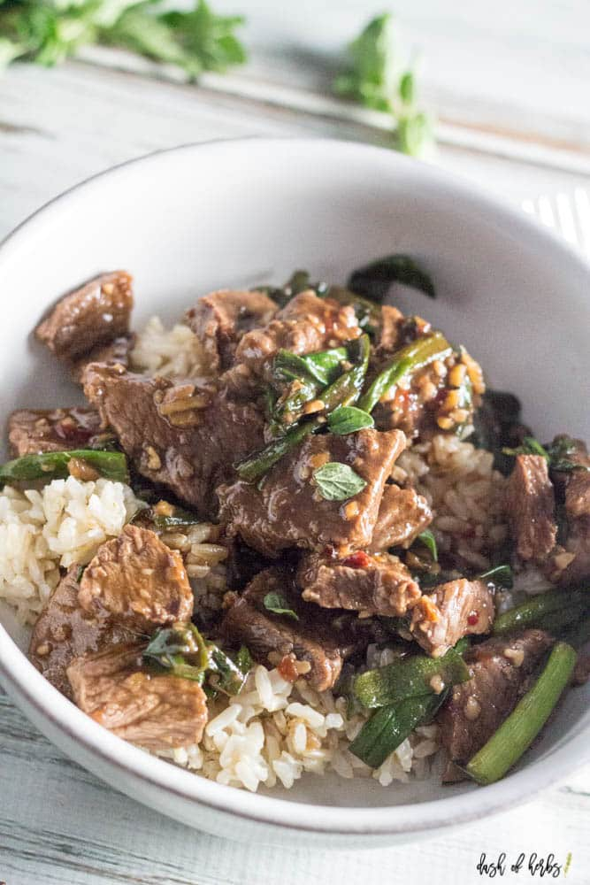 An close up image of the Skillet Mongolian Beef recipe.  You can see the beef, green onions and rice all in a white bowl.  There is also a fork next to the bowl.