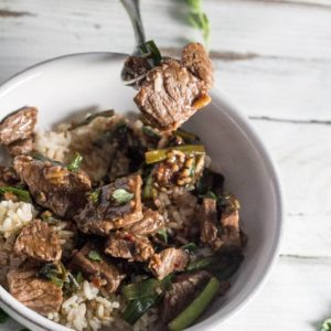 An overhead image of the Skillet Mongolian Beef recipe with a fork as the focal point. The fork has some of the beef as well as some green onions.