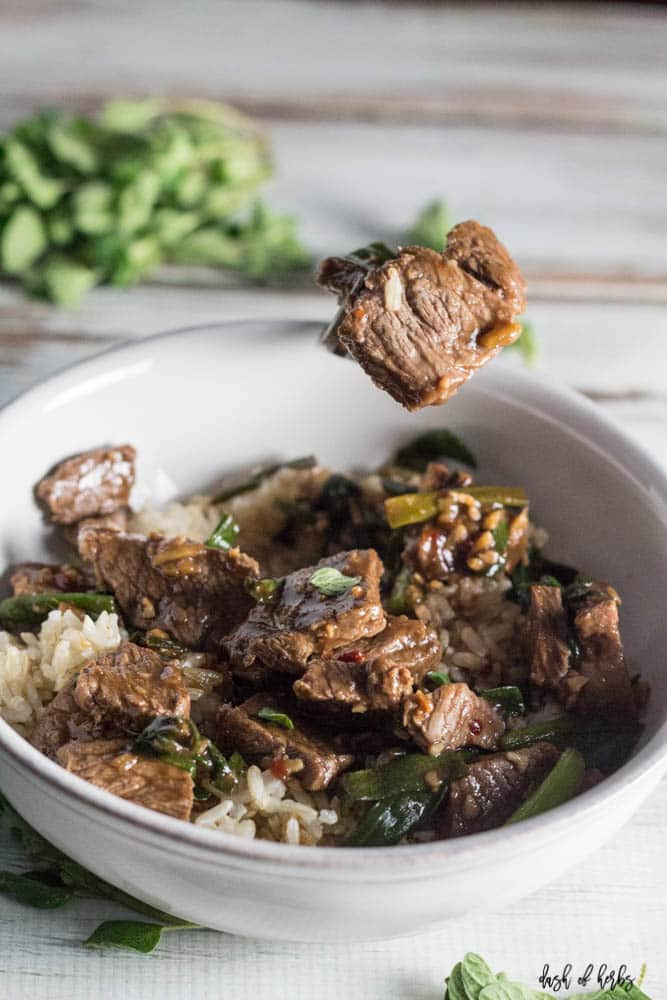 An overhead close up image of the Skillet Mongolian Beef recipe with a fork as the focal point.  The fork has some of the beef as well as some green onions.
