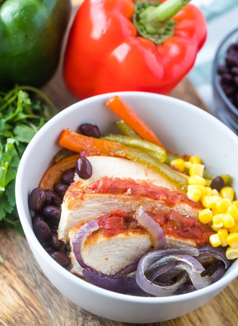 Bowl of sheet pan chicken fajita bowls with black beans, corn, peppers and red onions. A large green and red pepper are in the background with fresh cilantro.