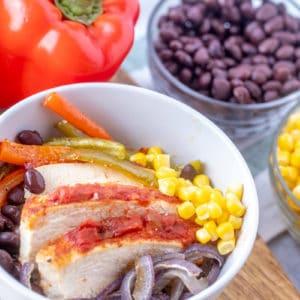 Bowl of sheet pan chicken fajita bowls with corn, red onions