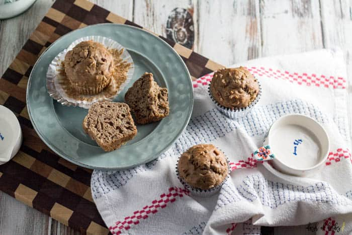 A horizontal overhead image of the Banana Nut Morning Glory Muffins recipe that shows two muffins on a small light blue plate. One of the muffins has been cut in half. There are two other muffins scattered throughout the image.
