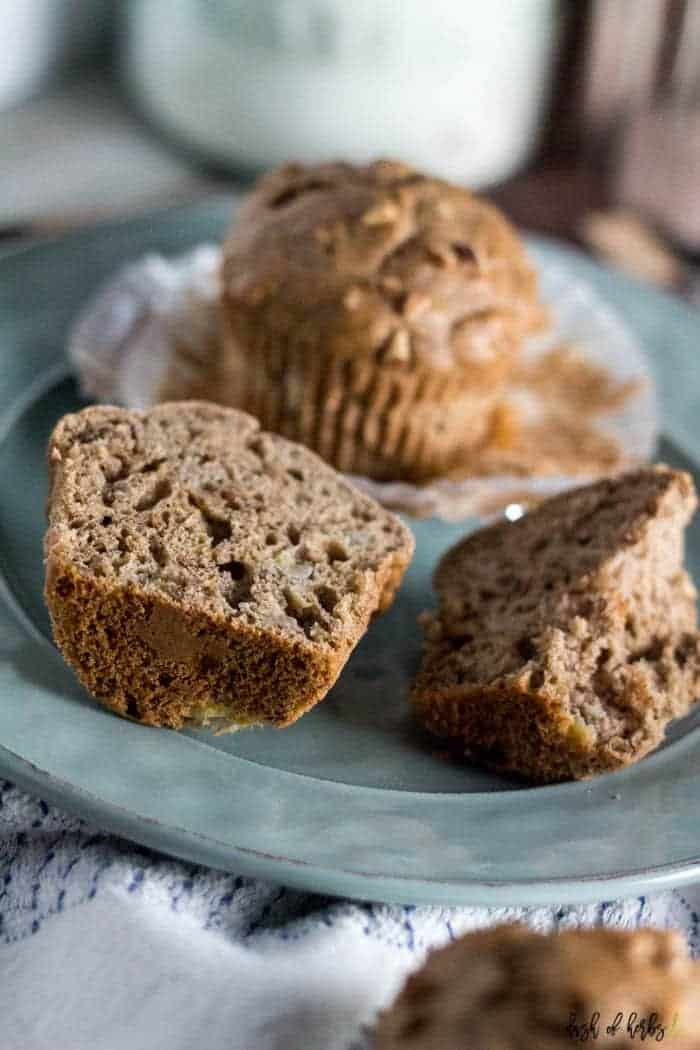 A close up image of the Banana Nut Morning Glory Muffins recipe that shows two muffins on a small light blue plate. One of the muffins has been cut in half.