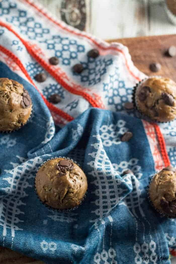 An image of the Chocolate Chip Zucchini Muffins recipe that shows 4 muffins on a colorful napkin. Chocolate chips are scattered throughout the image.