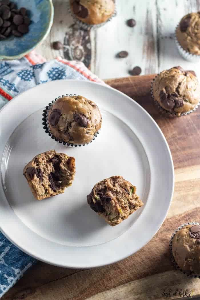 An image of the Chocolate Chip Zucchini Muffins recipe that shows two muffins on a white plate. One of the muffins on the plate has been cut in half. The remainder of the muffins and chocolate chips are scattered throughout the image.