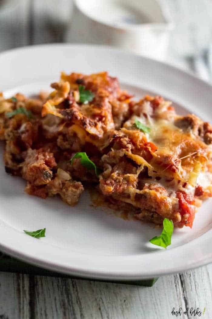 A close up image of the Turkey Lasagna recipe.  The recipe is on a white plate and clearly you can see the insides of the lasagna.  That includes cooked ground turkey, tomatoes, peppers, lasagna noodles and cheese.