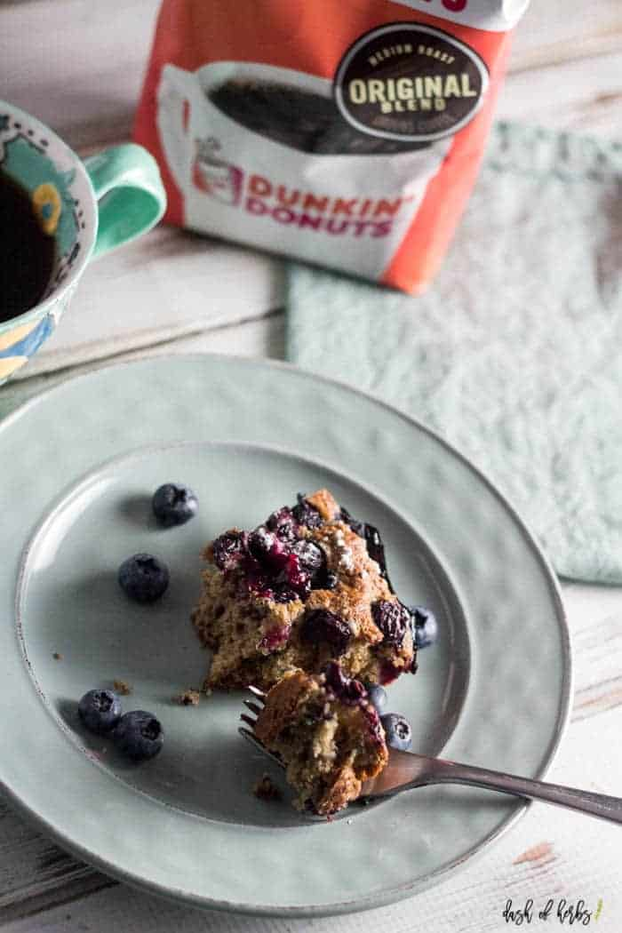 On a light blue plate, there is a slice of the blueberry coffee cake with a fork sitting on the plate.  There is also a cup of Dunkin Donuts coffee in the upper lefthand corner.