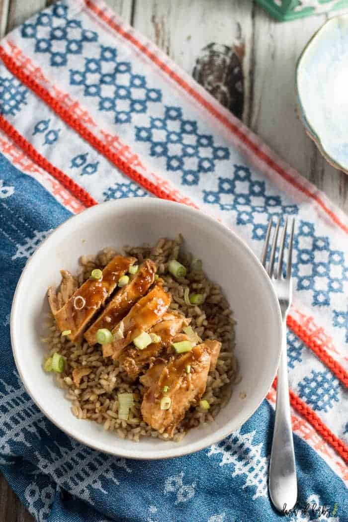 An overhead image of the Kid Friendly Baked Sweet and Sour Chicken with Rice recipe with chopped green onions in a white bowl.  There is a colorful napkin underneath the bowl.