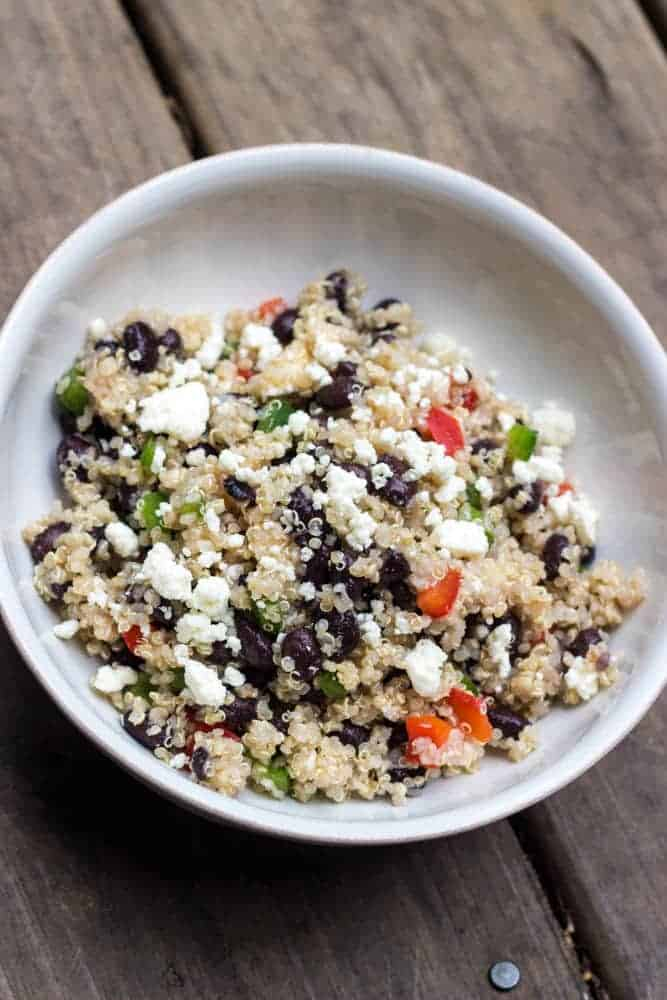This image is of the Healthy Black Bean Quinoa and Feta Salad recipe. The image is a close up that shows the black beans, quinoa, chopped raw peppers and feta cheese.