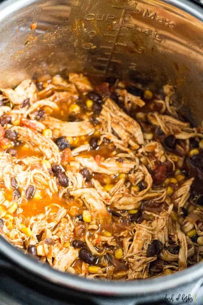 This image is a close up of the Instant Pot Salsa Chicken recipe in the Instant Pot. You can clearly see the black beans, shredded chicken and corn from the recipe.