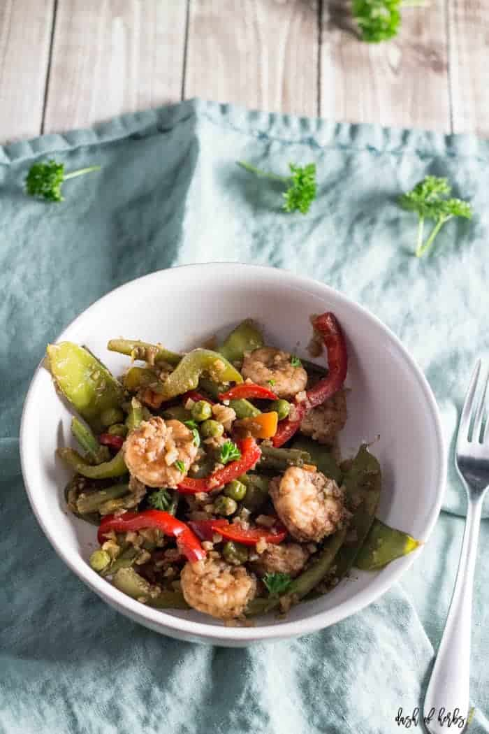 This close up image of Jerk Shrimp Stir Fry with Cauliflower Rice recipe is in a white bowl. There is a light blue napkin underneath the bowl.