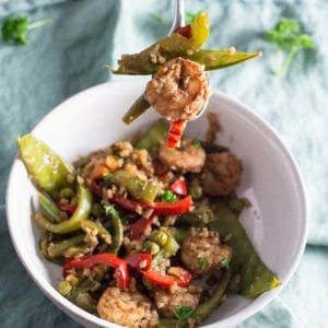 This image of Jerk Shrimp Stir Fry with Cauliflower Rice recipe is in a white bowl. There is a fork above the bowl that shows the shrimp and veggies on it. There is a small light blue napkin underneath the bowl.