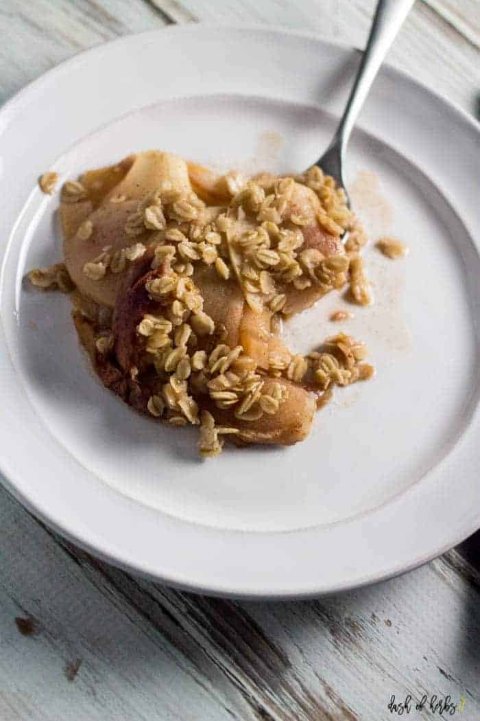 An image of the slow cooker apple peach crumble recipe. A spoonful of the dessert is on a white plate showing the peach chunks and oats. A spoon has a bite of this recipe on it for you to enjoy.