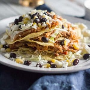 An image of the Slow Cooker Salsa Chicken Tostadas recipes on a white plate. There are 3 tostadas stacked on top of each other with black beans, corn and lettuce on the plate. There is a navy blue napkin underneath the plate.