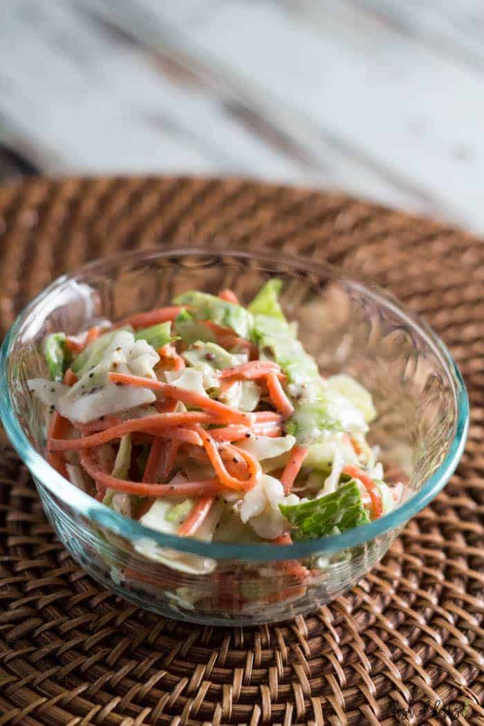An image of the Spicy Creamy Coleslaw recipe is in a clear bowl.  The bowl is on a brown rattan charger.