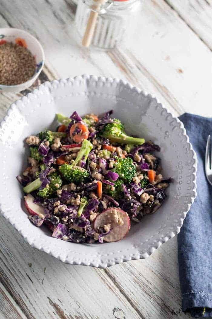 An image of the Asian Chopped Salad with Turkey recipe in a decorative cream ceramic bowl.  This image is a close up of the recipe.  There is a napkin in the image that is navy blue.
