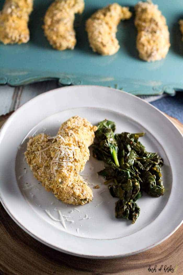 An image of the baked cornmeal chicken and greens recipe on a white plate.  The image has one chicken breast with the cooked greens.  There is a tray of chicken tenders in the background.