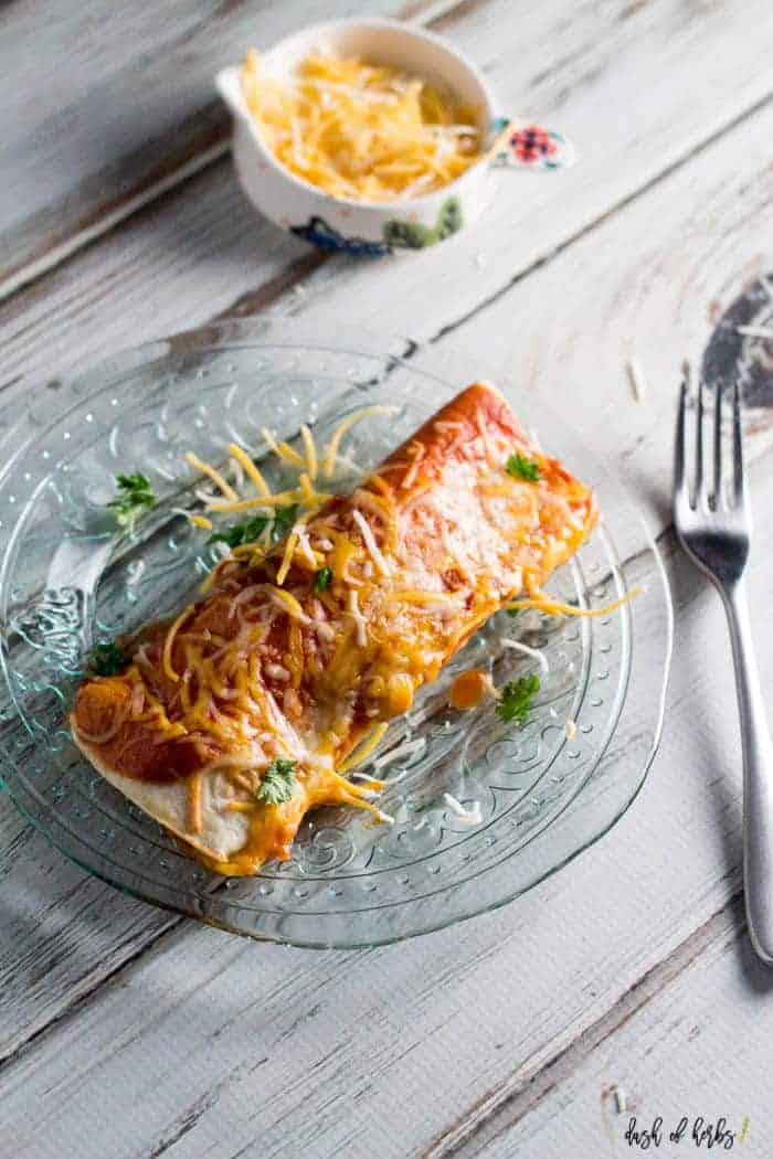 An image of the Instant Pot chicken enchiladas recipe on a clear glass plate. There is a small bowl with shredded cheese in the background of the image.