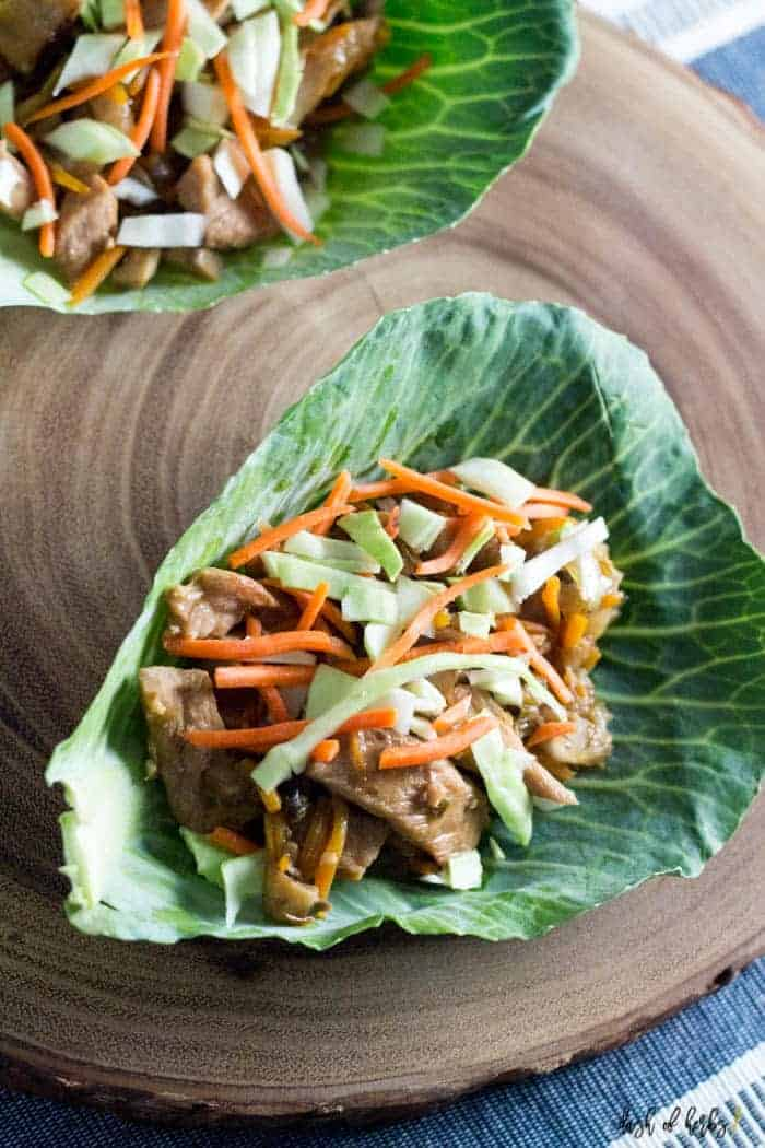 "An image of the Instant Pot Low-Carb Mu Shu Pork Tacos recipe with the Mu Shu pork on beds of cabbage. The ""tacos"" are on a wooden slab."