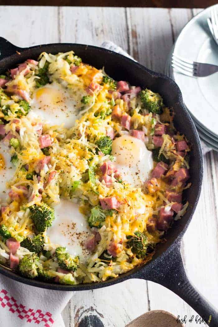An image of the breakfast hash brown skillet in a large cast iron skillet. The image is a close up showing the ingredients of ham, eggs and broccoli. In the upper lefthand side, there is a stack of white plates and forks for serving.