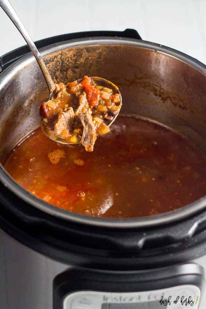 A photo of the spicy Instant Pot steak chili recipe in the Instant Pot. A large ladle shows the steak chili.
