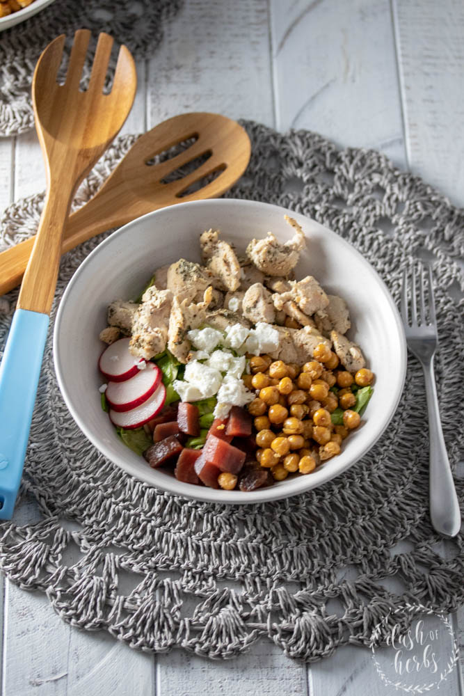 Salad bowl with grilled chicken, roasted chickpeas, beets and butter lettuce with salad spoons. Recipe from Blue Apron for WW.