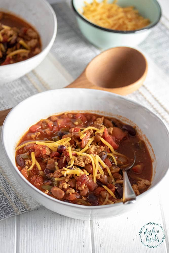 A close up photo of a bowl of Instant Pot Turkey Chili with cheese. A side of shredded cheese is in the upper righthand corner with another bowl of instant pot turkey chili in the background.
