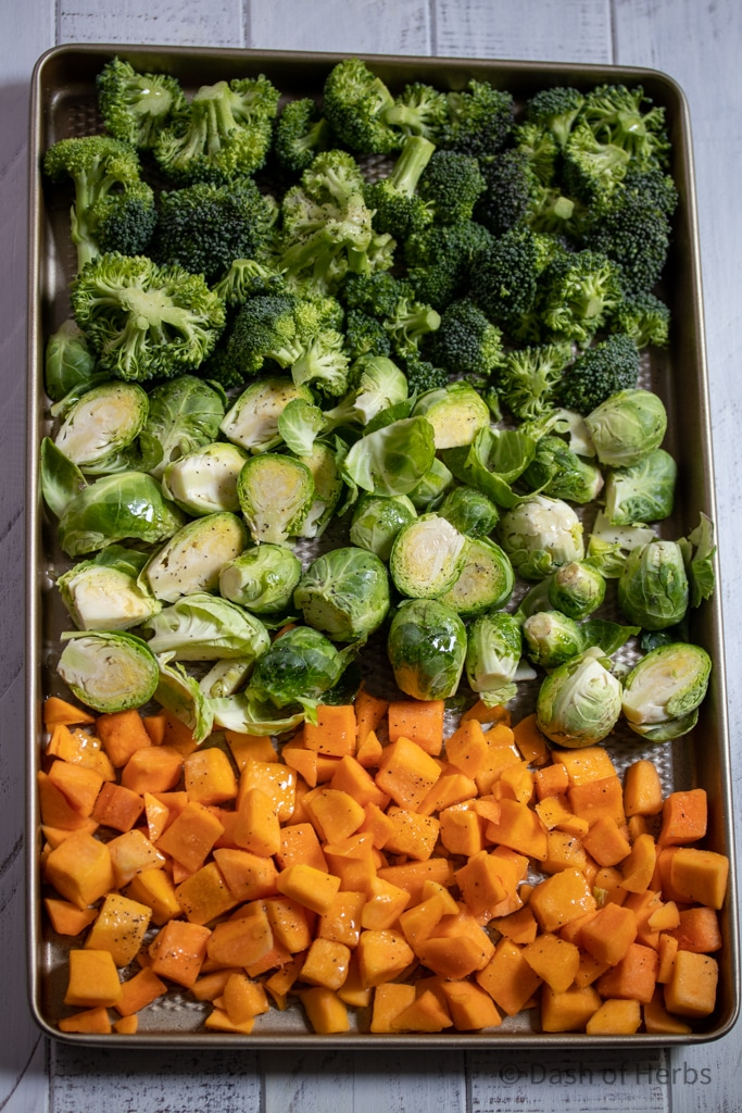 Butternut squash, brussel spouts and broccoli on a pan ready to be placed in the oven.